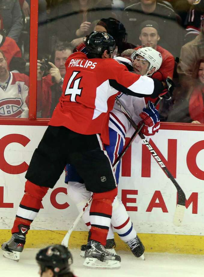Montreal Canadiens' Erik Cole (72) is checked by Ottawa Senators' Chris Phillips during the second period of NHL hockey game in Ottawa, Wednesday, Jan. 30, 2013. (AP Photo/The Canadian Press, Fred Chartrand) Photo: FRED CHARTRAND