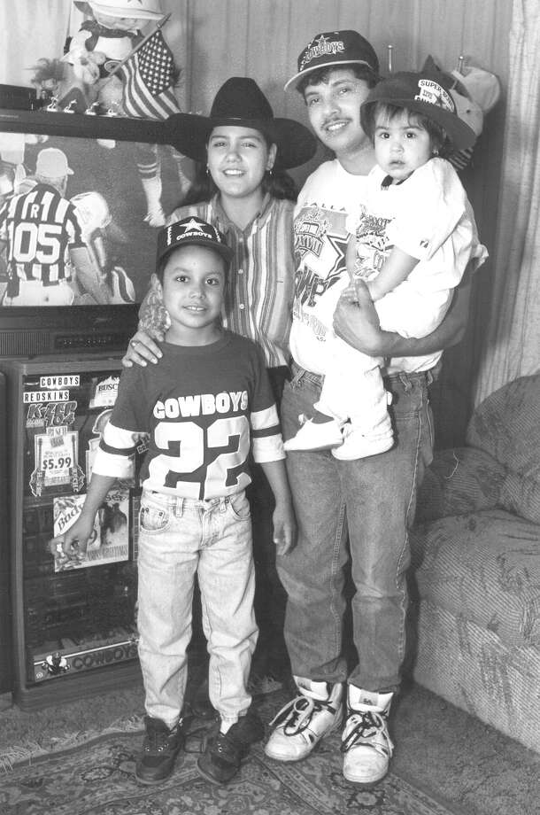 Cowboys fans Sandra Martinez, George Beltran Sr., Ashley Martinez, 17 months, and George Beltran Jr., 7, watch Super Bowl XXVII at Beltran's home in San Antonio on Jan. 31, 1993. Photo: San Antonio Express-News File Photo