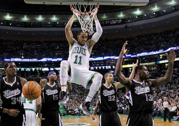 Boston Celtics guard Courtney Lee (11) hangs on after a dunk as Sacramento Kings forward Jason Thompson (34), center DeMarcus Cousins (15), guard Francisco Garcia (32) and guard Tyreke Evans (13) react during the first half of an NBA basketball game in Boston, Wednesday, Jan. 30, 2013. Offensive interference was ruled and the basket did not count. (AP Photo/Elise Amendola) Photo: Elise Amendola