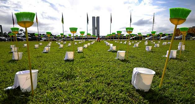 "Demonstrators place 81 cleaning kits consisting each in a broom, a bucket and a duster in front of the Brazilian National Congress, in Brasilia, on January 30, 2013. The demonstration is organized by Rio de Janeiro's ""River of Peace"" movement and the 81 cleaning kits --the number of senators of in the national congress-- symbolizes the need for ""cleaning"" the senate of corruption. This week the presidential election will be held in the federal senate and the favorite candidate, senator Renan Calheiros, has been the target of many accusations of corruption. Photo: Pedro Ladeira, AFP/Getty Images"