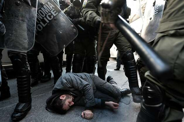 An injured protester lays on the street outside the Labour Ministry in Athens on January 30, 2013. Police were called in on Wednesday to dislodge around 30 Communist unionists from the labour ministry in a protest against new pension cut plans. The unionists were arrested and police used tear gas outside the building to disperse a larger group of protesters demanding their release. Photo: Aris Messinis, AFP/Getty Images