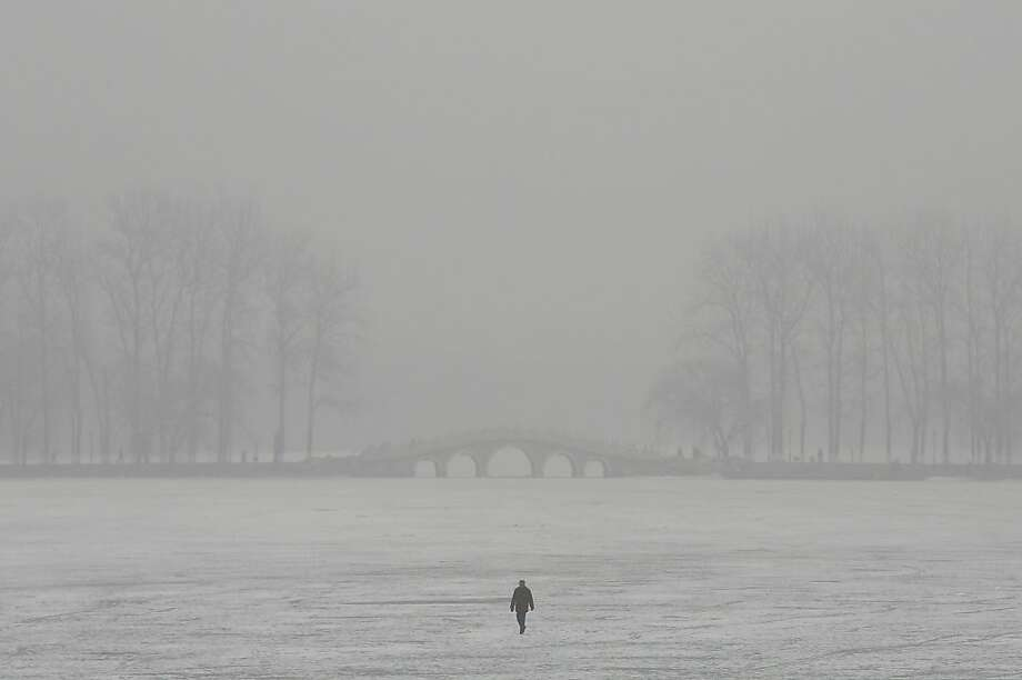 A man walks on a frozen lake during severe pollution on January 30, 2013 in Beijing, China. The fourth round of heavy smog to hit Beijing in one month has sent more people to the hospital with respiratory illnesses and prompted calls for legislation to curb pollution. The haze choking many Chinese cities covers a total area of 1.3 million square kilometers, the China's Ministry of Environmental Protection said Tuesday. Photo: Feng Li, Getty Images