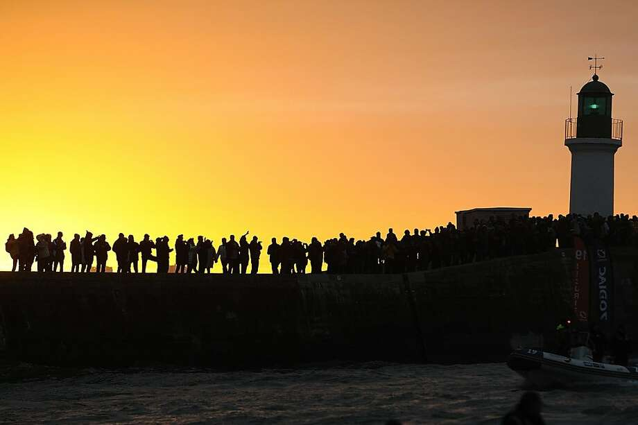 Circumnavigator makes landfall: The arrival of the monohull Hugo Boss and its English skipper, Alex Thomson, draw spectators to a seawall at Les Sables d'Olonne, France. Thomson placed third in the Vendee Globe solo round-the-world race. Photo: Jean-Sebastien Evrard, AFP/Getty Images