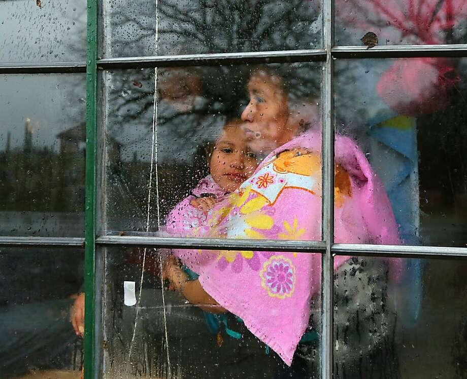 """Fanyumi Lopez hugs her four-year-old daughter, Rucelmi, as the family waits for help after a tree fell on her mobile home in Adairsville, Georgia on Wednesday, January 30, 2013. """"I prayed everything will come back to normal and at the end a door will open,"""" Lopez said. Photo: Curtis Compton, McClatchy-Tribune News Service"""