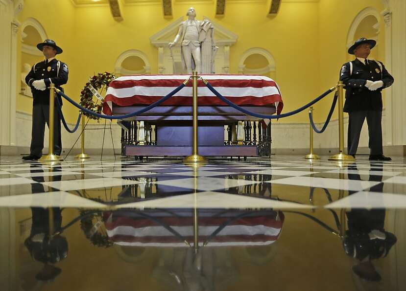 A Capitol police honor guard stand watch over the casket containing the body of former Virginia Supr
