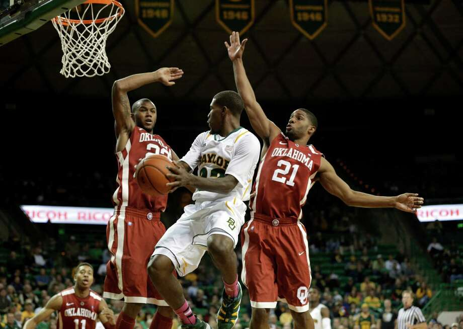 Baylor 's A.J. Walton (22) passes the ball as Oklahoma 's Amath M'Baye (22) and Cameron Clark (21) defend in the second half of an NCAA college basketball game Wednesday, Jan. 30, 2013, in Waco, Texas. Oklahoma won 74-71. (AP Photo/Tony Gutierrez) Photo: Tony Gutierrez, Associated Press / AP