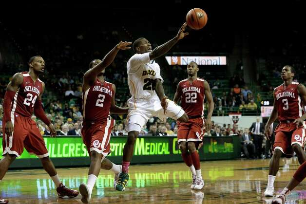 Baylor guard A.J. Walton (22) is forced to pass the ball under pressure from Oklahoma 's Romero Osby (24), Steven Pledger (2) , Amath M'Baye (22), and Buddy Hield (3) in the second half of an NCAA college basketball game Wednesday, Jan. 30, 2013, in Waco, Texas. Oklahoma won 74-71. (AP Photo/Tony Gutierrez) Photo: Tony Gutierrez, Associated Press / AP