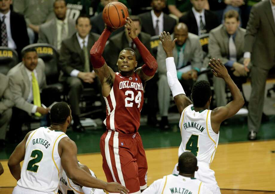 Oklahoma 's Romero Osby (24) looks to pass the ball under pressure from Baylor 's Rico Gathers (2) and Gary Franklin (4) in the first half of an NCAA college basketball game Wednesday, Jan. 30, 2013, in Waco, Texas. (AP Photo/Tony Gutierrez) Photo: Tony Gutierrez, Associated Press / AP