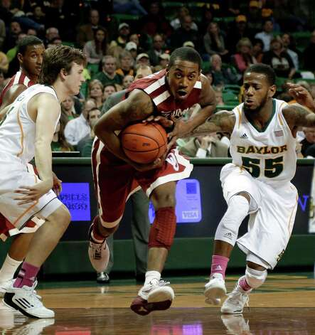 Baylor's Brady Heslip, left, and Pierre Jackson, defend as Oklahoma's Je'lon Hornbeak (5) finds an opening to the basket during the first half of an NCAA college basketball game Wednesday, Jan. 30, 2013, in Waco, Texas. (AP Photo/Tony Gutierrez) Photo: Tony Gutierrez, Associated Press / AP
