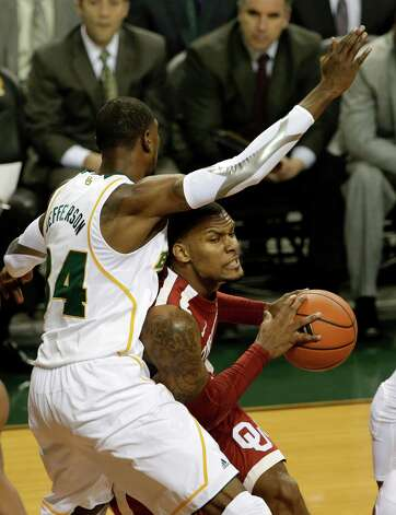 Baylor 's Cory Jefferson (34) defends against a drive to the basket by Oklahoma 's Romero Osby, right, during the first half of an NCAA college basketball game Wednesday, Jan. 30, 2013, in Waco, Texas. (AP Photo/Tony Gutierrez) Photo: Tony Gutierrez, Associated Press / AP