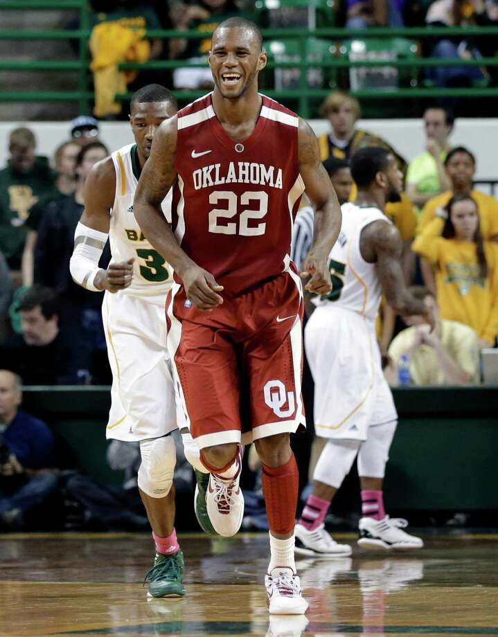Oklahoma 's Amath M'Baye (22) smiles as he runs back up court after sinking a three-point basket in the second half of an NCAA college basketball game against Baylor Wednesday, Jan. 30, 2013, in Waco, Texas. Baylor's Cory Jefferson, left rear, and Pierre Jackson, right rear, are shown behind on the play. Oklahoma won 74-71. (AP Photo/Tony Gutierrez) Photo: Tony Gutierrez, Associated Press / AP