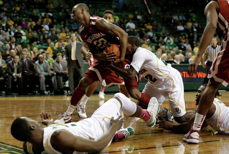Baylor 's Deuce Bello, bottom left, and Rico Gathers, bottom right, watch as A.J. Walton, center right, struggles with Oklahoma 's Amath M'Baye (22) for control of a rebound in the second half of an NCAA college basketball game Wednesday, Jan. 30, 2013, in Waco, Texas. M'Baye had 20-points in the 74-71 Oklahoma win. (AP Photo/Tony Gutierrez) Photo: Tony Gutierrez, Associated Press / AP