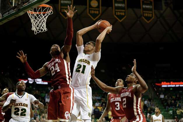 Baylor 's Isaiah Austin (21) attempts a shot as Oklahoma 's Romero Osby (24), Buddy Hield (3) and Steven Pledger (2) defend in the second half of an NCAA college basketball game Wednesday, Jan. 30, 2013, in Waco, Texas. Oklahoma won 74-71. (AP Photo/Tony Gutierrez) Photo: Tony Gutierrez, Associated Press / AP