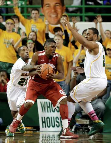 Baylor fans hold a large photo cut out of head coach Scott Drew, rear, as A.J. Walton, left, and Rico Gathers, right, defend against Oklahoma 's Andrew Fitzgerald, center, during the second half of an NCAA college basketball game Wednesday, Jan. 30, 2013, in Waco, Texas. Oklahoma won 74-71.  (AP Photo/Tony Gutierrez) Photo: Tony Gutierrez, Associated Press / AP