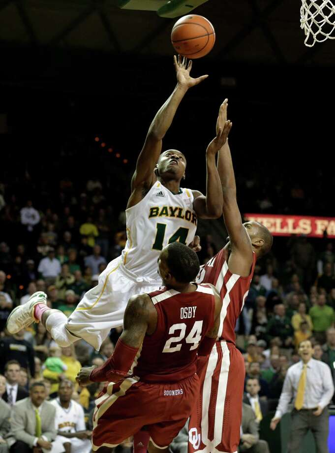 Baylor's Deuce Bello (14) goes up for a shot as Oklahoma's Romero Osby (24) and Amath M'Baye, right, defend during the second half of an NCAA college basketball game Wednesday, Jan. 30, 2013, in Waco, Texas. Bello was charged with an offensive foul on the play. Oklahoma won 74-71. (AP Photo/Tony Gutierrez) Photo: Tony Gutierrez, Associated Press / AP