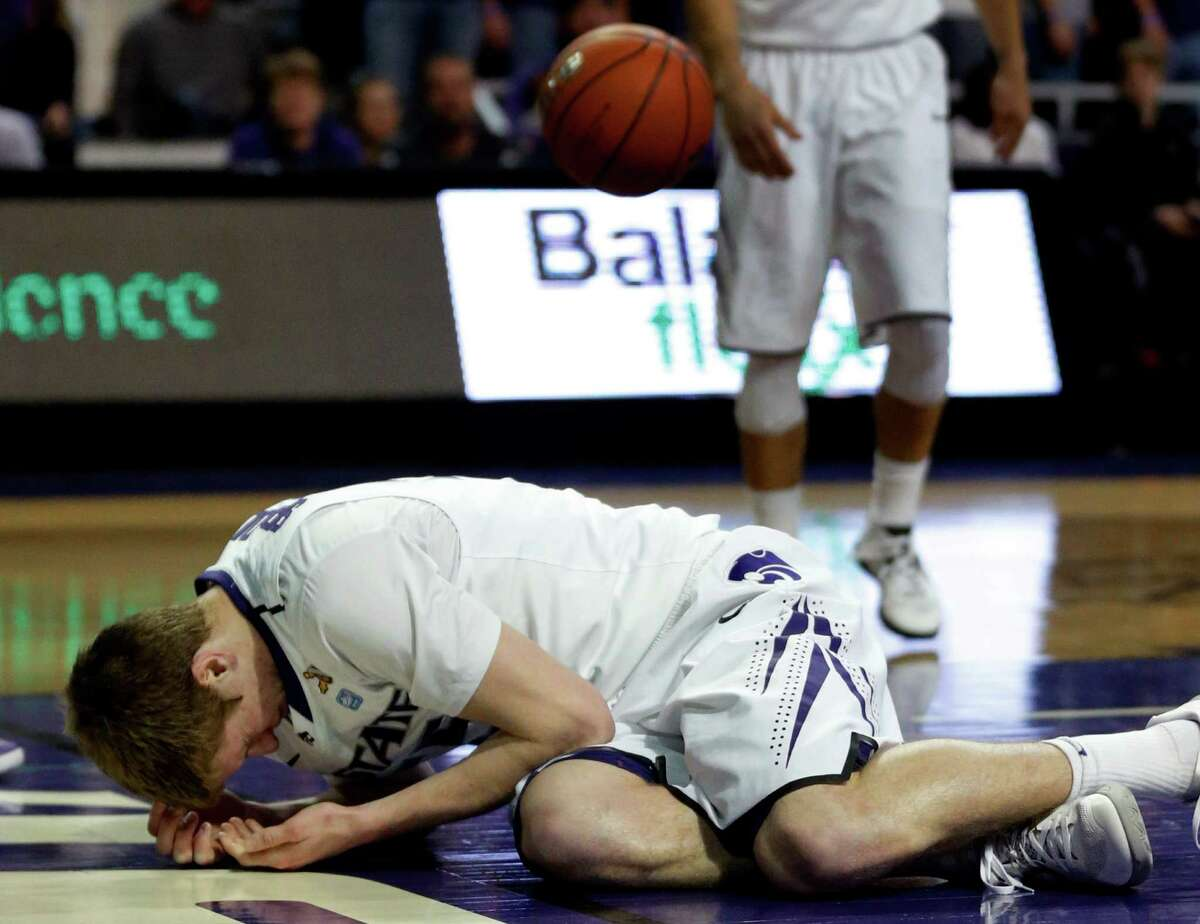 Kansas State guard Will Spradling (55) lands on the floor after getting hit on the nose during the first half of an NCAA college basketball game against the Texas in Manhattan, Kan., Wednesday, Jan. 30, 2013. Kansas State defeated Texas 83-57. (AP Photo/Orlin Wagner)