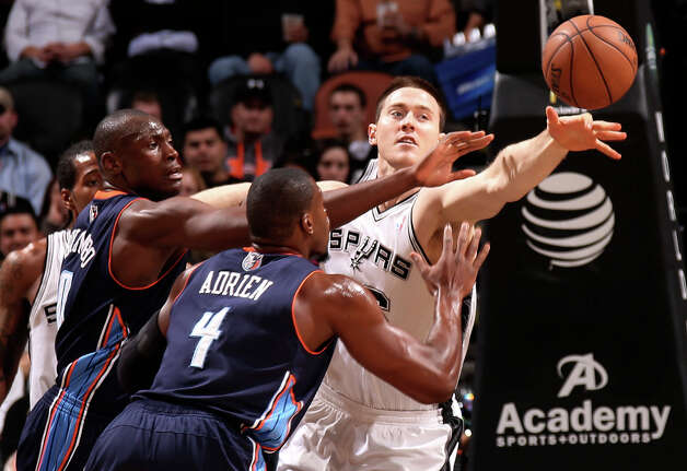 San Antonio Spurs Aron Baynes keeps the ball away from Charlotte Bobcats' Bismack Biyombo, left and Jeff Adrien during the first half at the AT&T Center, Wednesday, Jan. 30, 2013. Photo: Jerry Lara, San Antonio Express-News / © 2013 San Antonio Express-News