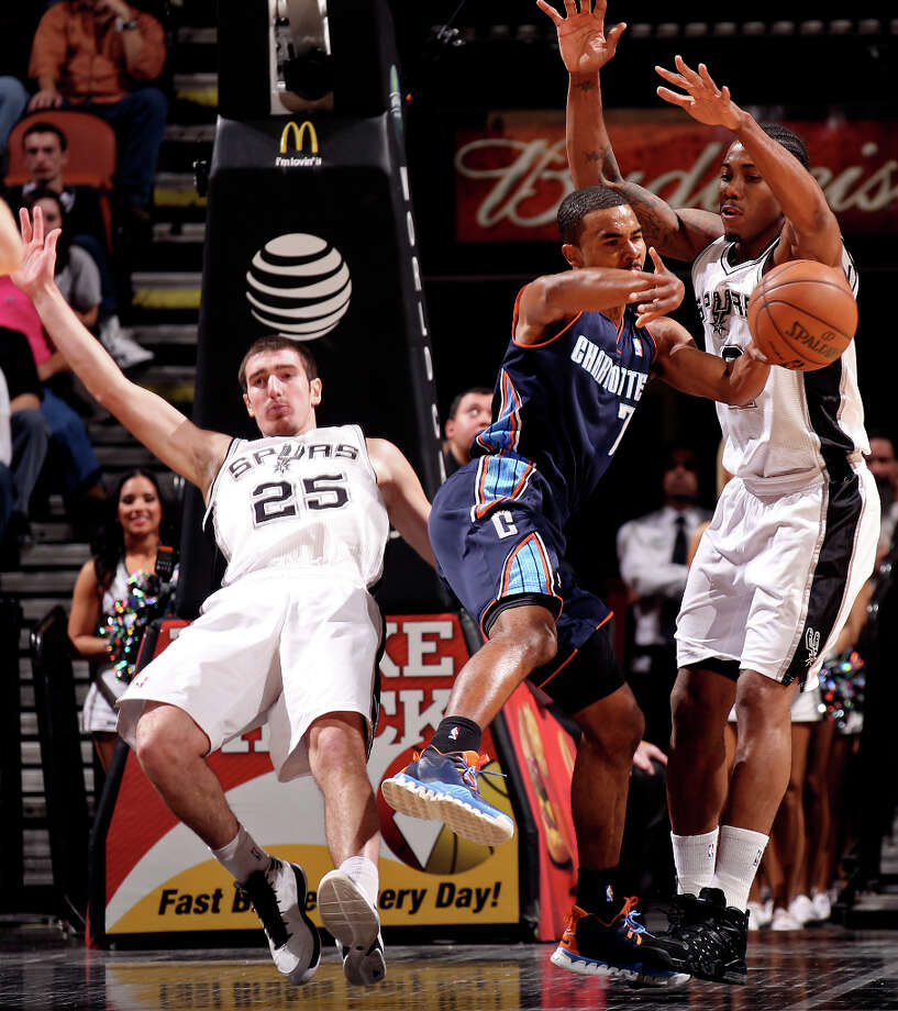 Charlotte Bobcats' Ramon Sessions passes out to the perimeter under pressure from San Antonio Spurs' Nando De Colo, left, and Kawhi Leonard during the first half at the AT&T Center, Wednesday, Jan. 30, 2013. Photo: Jerry Lara, San Antonio Express-News / © 2013 San Antonio Express-News