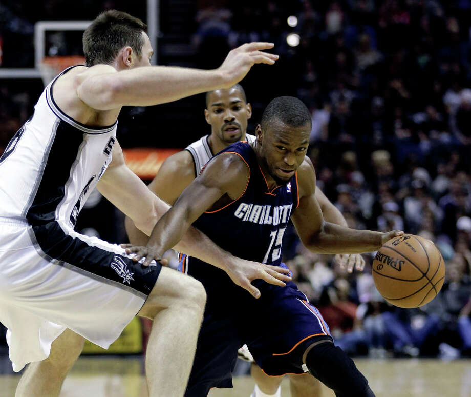 Charlotte Bobcats' Kemba Walker (15) drives around San Antonio Spurs' Aron Baynes, left, during the second half of an NBA basketball game, Wednesday, Jan. 30, 2013, in San Antonio. Photo: Eric Gay, Associated Press / AP