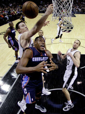 San Antonio Spurs' Aron Baynes, left, reaches over Charlotte Bobcats' Bismack Biyombo, center, for a rebound during the first half of an NBA basketball game, Wednesday, Jan. 30, 2013, in San Antonio. San Antonio Spurs' Manu Ginobili, right, of Argentina, watches. Photo: Eric Gay, Associated Press / AP
