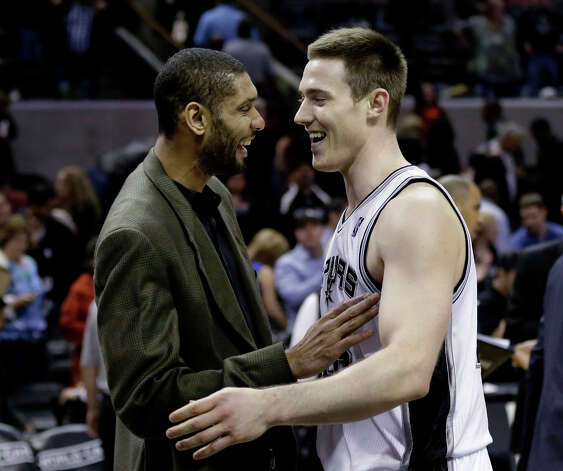 San Antonio Spurs' Tim Duncan, left, greets teammate Aron Baynes, right, after an NBA baseketball game against the Charlotte Bobcats, Wednesday, Jan. 30, 2013, in San Antonio. Duncan did not play due to a sore knee. Photo: Eric Gay, Associated Press / AP