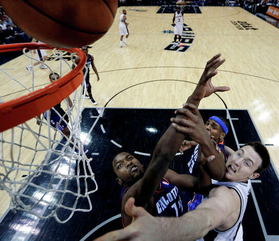 San Antonio Spurs Aron Baynes, right, scores over Charlotte Bobcats' Michael Kidd-Gilchrist (14) and Brendan Haywood (33) during the second half of an NBA basketball game, Wednesday, Jan. 30, 2013, in San Antonio. Photo: Eric Gay, Associated Press / AP