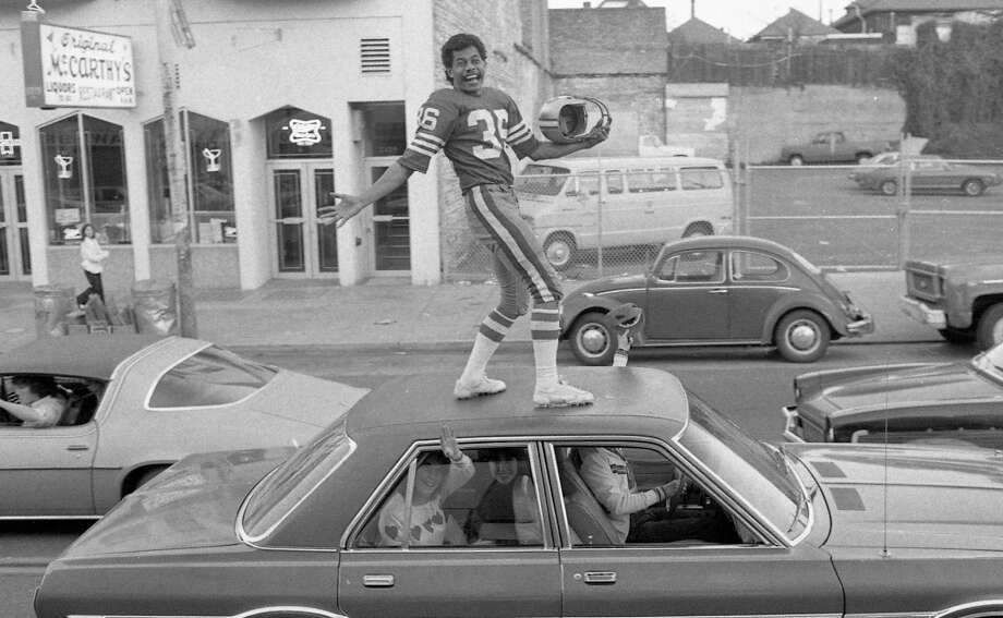 MISSION DISTRICT: Spirits were high but arrests low in the Mission after the 49ers Super Bowl XVI win. We absolutely can't endorse roof surfing on a 1970s Chrysler Cordoba. But if you're going to do it, wear a full Paul Hofer uniform complete with helmet. Photo: John O'Hara, The Chronicle / ONLINE_YES