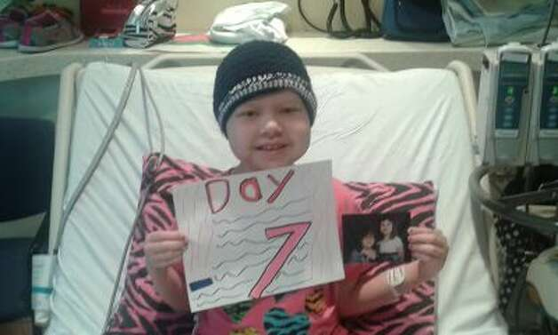 Mackenzie holds up a picture of her and her sister as a countdown until her bone marrow transplant. Photo: Gay DeRouen