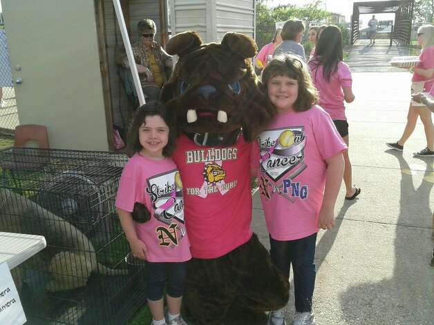 Mackenzie, left, and Sabrina, right, pose for a picture with a mascot for a benefit. Photo: Gay DeRouen