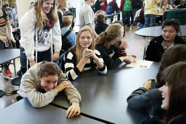 "In this Jan. 18, 2013 photo, Chanhassen High School students relax during their 20-minute ""recess"" in the commons area Jan. 18, 2013 in Chanhassen, Minn.  Chanhassen is among a small but growing number of schools that has homework-free nights scattered throughout the school year along with the ""recess"" breaks two days a week where students chat, catch up on homework, rest, play games like hackie sack or grab a snack. (AP Photo/Jim Mone) Photo: Jim Mone, STF / AP"