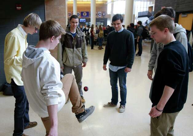 "In this Jan. 18, 2013 photo, Chanhassen High School students play a game of hackie sack relax during their 20-minute ""recess"" in the school's theater Jan. 18, 2013 in Chanhassen, Minn.  Chanhassen is among a small but growing number of schools that has homework-free nights scattered throughout the school year along with the ""recess"" breaks two days a week where students chat, catch up on homework, rest, play games like hackie sack or grab a snack. (AP Photo/Jim Mone) Photo: Jim Mone, STF / AP"