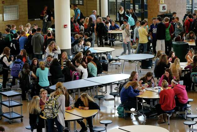 "In this Jan. 18, 2013 photo, Chanhassen High School students relax during a 20-minute ""recess"" in the cafeteria commons area during a stress break Jan. 18, 2013 in Chanhassen, Minn.  Chanhassen is among a small but growing number of schools that has homework-free nights scattered throughout the school year along with the ""recess"" breaks two days a week where students chat, catch up on homework, rest, play games like hackie sack or grab a snack. (AP Photo/Jim Mone) Photo: Jim Mone, STF / AP"