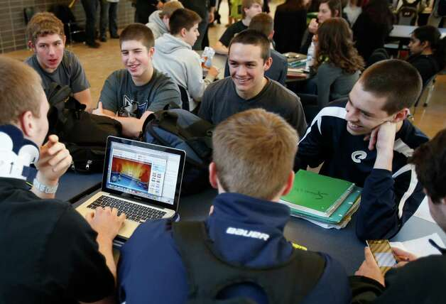 "In this Jan. 18, 2013 photo, Chanhassen High School students relax while another plays a computer game during a 20-minute ""recess"" in the cafeteria commons area during a stress break Jan. 18, 2013 in Chanhassen, Minn.  Chanhassen is among a small but growing number of schools that has homework-free nights scattered throughout the school year along with the ""recess"" breaks two days a week where students chat, catch up on homework, rest, play games like hackie sack or grab a snack. (AP Photo/Jim Mone) Photo: Jim Mone, STF / AP"