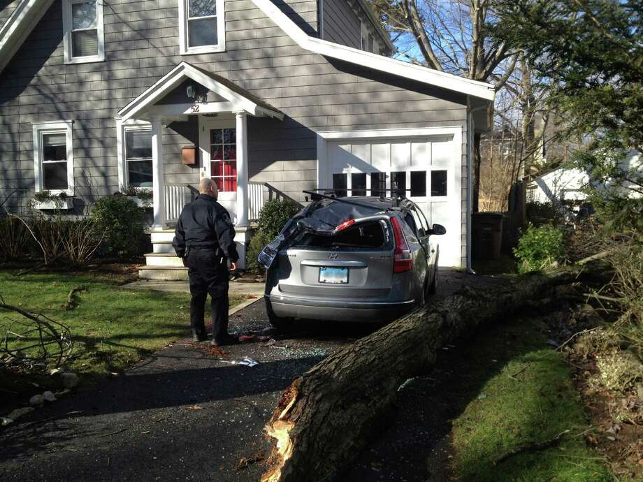 A tree limb fell on top of a car parked in a driveway on Bon Air Avenue in Springdale Thursday morning as strong winds gusted through the area. Photo: John Nickerson