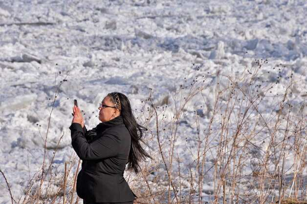 Brandie Dingman of Fultonville stops on her lunch hour walk to take a picture of an ice jam on the Mohawk River at the Stockade in Schenectady Thursday Jan. 31, 2013.  (John Carl D'Annibale / Times Union) Photo: John Carl D'Annibale