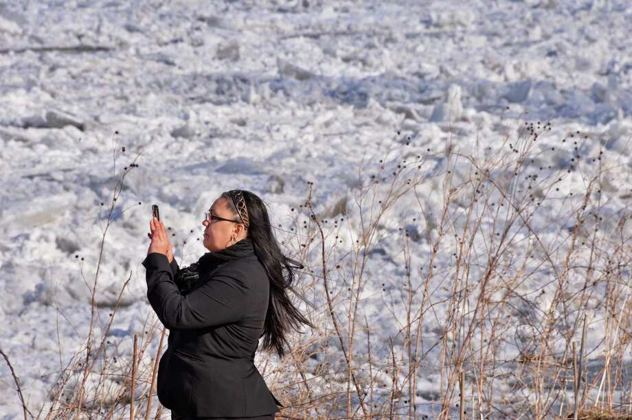 Brandie Dingman of Fultonville stops on her lunch hour walk to take a picture of an ice jam on the Mohawk River at the Stockade in Schenectady Thursday Jan. 31, 2012.  (John Carl D'Annibale / Times Union) Photo: John Carl D'Annibale