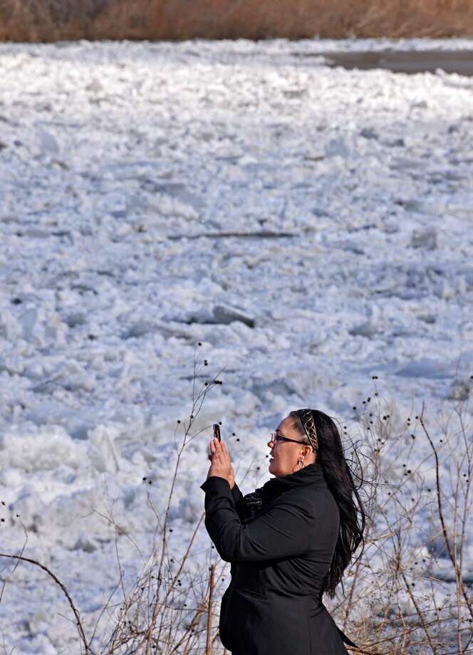 Brandie Dingman of Fultonville stops on her lunch hour walk to take a picture of an ice jam on the Mohawk River at the Stockade in Schenectady Thursday Jan. 31, 2013.  (John Carl D'Annibale / Times Union) Photo: John Carl D'Annibale / 00020994A