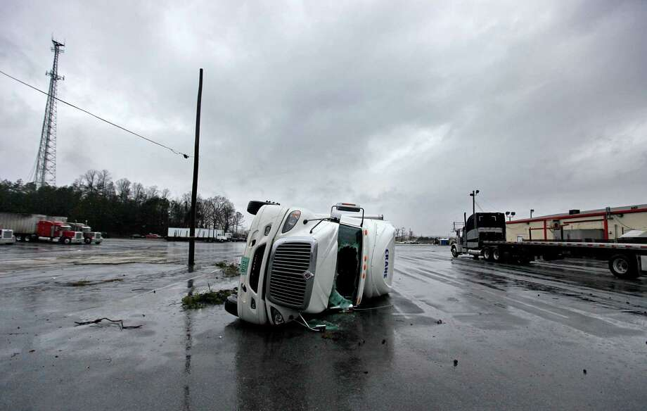 An overturned tractor trailer sits in a parking lot following a tornado, Wednesday, Jan. 30, 2013, in Adairsville, Ga. A fierce storm system that roared across Georgia has left at least one person dead after it demolished buildings and flipped vehicles on Interstate 75 northwest of Atlanta. Photo: David Goldman, AP / AP
