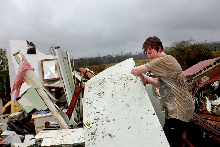 Will Carter, 15, pulls up debris while searching for the family dog, a pit bull named Niko, upon arriving to his damaged home from school following a tornado, Wednesday, Jan. 30, 2013, in Adairsville, Ga. A fierce storm system that roared across Georgia has left at least one person dead after it demolished buildings and flipped vehicles on Interstate 75 northwest of Atlanta. Photo: David Goldman, AP / AP