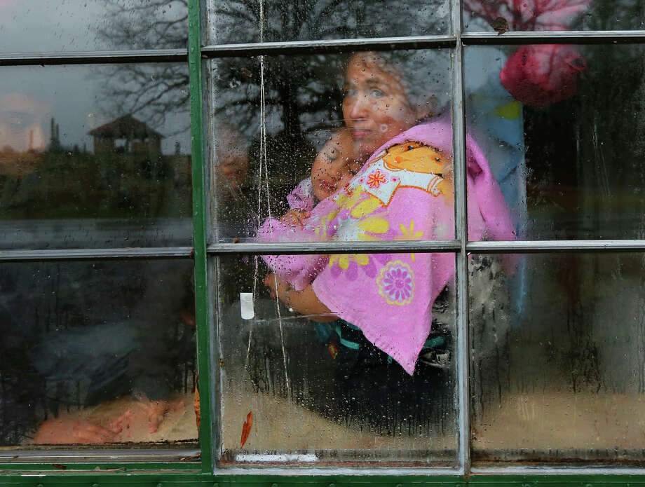 "Fanyumi Lopez, 38, covers up with a towel and hugs her 4-year-old daughter Rucelmi looking out her window as the family waits for help after a tree fell on and destroyed half their mobile home in Jack Craig's Trailer Park in Adairsville, Ga. in an apparent tornado on Wednesday, Jan. 30, 2013. Lopez said "" I prayed everything will come back to normal and at the end a door will open"" during the storm. She was alone when the storm hit. Photo: Curtis Compton, AP / Atlanta Journal-Constitution"