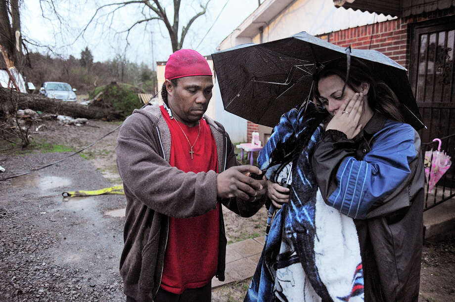 Darrell Lockridge consoles his wife Samantha in Bordeaux section of Nashville, Tenn., Wednesday Jan. 30, 2013.  Her uncle, Vernon Hartsell was killed when a large tree fell on the shed where he was taking shelter.  (AP Photo/The Tennessean, John Partipilo)  NO SALES Photo: JOHN PARTIPILO, AP / The Tennessean
