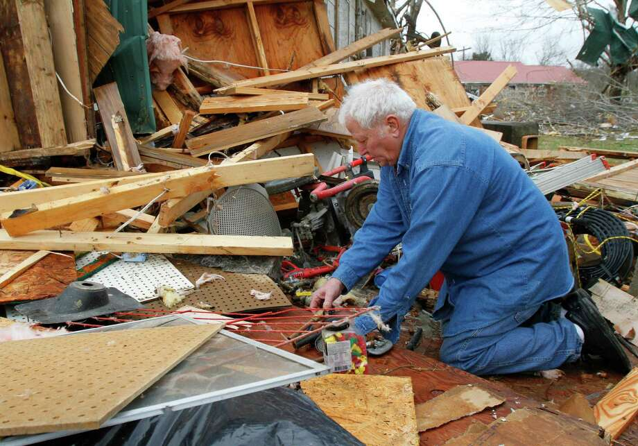 Ronnie Shanes searches through debris of his brother's home after a storm ripped through Coble, Tenn. early Wednesday, Jan. 30, 2013. A large storm system packing high winds, hail and at least one tornado tore across a wide swath of the South and Midwest on Wednesday, killing one person, blacking out power to thousands and damaging homes. Photo: Butch Dill, AP / FR111446 AP