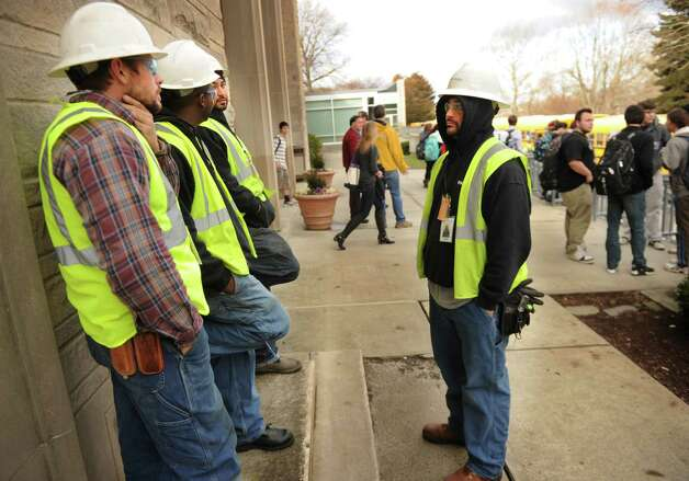Workers from roofing company Tecta America wait outside Fairfield Ludlowe High School to work on the wind damaged roof as students are dismissed early on Thursday, January 31, 2013. Photo: Brian A. Pounds
