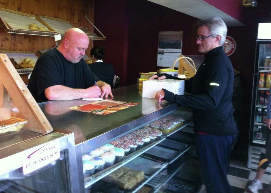 Rick Dickinson, owner of Great Cakes in Westport, takes a cake order from Chris Ahlgrim, a longtime patron who also bought a dozen cupcakes. Ahlgrim was one of many customers to support the shop after word got out that Dickinson would have to close shop if he did not come up with $4,000 for a town tax bill. Photo: Michael C. Juliano/Staff Photo