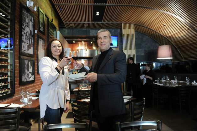 Cotto Wine Bar Pizzeria owners Silvy and Claudio Ridolfi, stand in their new Italian restaurant, in downtown Stamford, Conn., Thursday, Jan. 31, 2013. Photo: Helen Neafsey / Greenwich Time