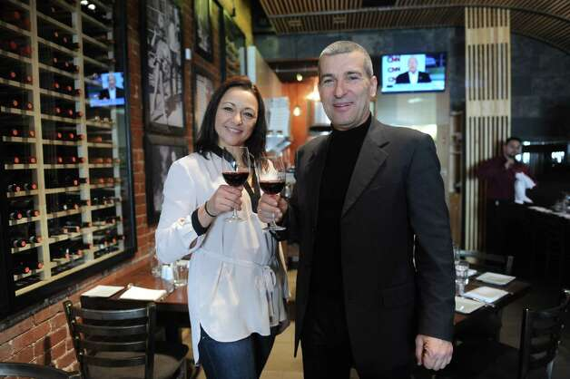 Silvy and Claudio Ridolfi, owner of Cotto Wine Bar Pizzeria, a new Italian restaurant, pose with a glass of wine in their restaurant in downtown Stamford, Conn., Thursday, Jan. 31, 2013. Photo: Helen Neafsey / Greenwich Time