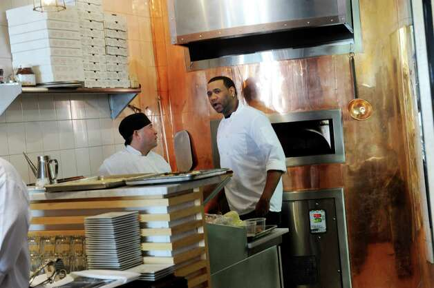 Chefs Rudy Martinez, left, and Melech Castillo work in the kitchen at Cotto Wine Bar Pizzeria, a new Italian restaurant in downtown Stamford, Conn., Thursday, Jan. 31, 2013. Photo: Helen Neafsey / Greenwich Time