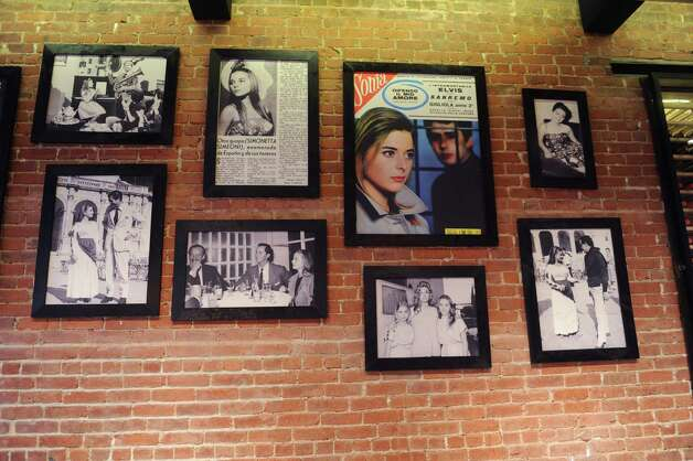 The interior of Cotto Wine Bar Pizzeria shows pictures of owner Silvy Ridolfi's mother, Simonetta Simeoni, a actress in Italy, in their new Italian restaurant, in downtown Stamford, Conn., Thursday, Jan. 31, 2013. Photo: Helen Neafsey / Greenwich Time