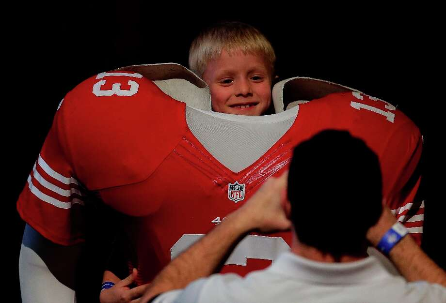 Perched above a cutout of a San Francisco 49ers football player, Matt Meyer, 7, poses for his father Ken Meyer, at the NFL experience Wednesday, Jan. 30, 2013, in New Orleans. The city will host the Super Bowl XLVII football game between the Baltimore Ravens and the San Francisco 49ers Sunday. Photo: Charlie Riedel, Associated Press / AP
