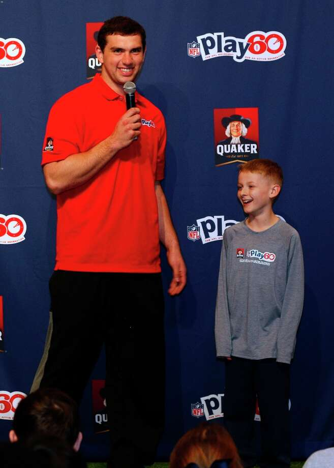 Andrew Luck introduces Hunter Paulin, winner of the NFL Play 60 Super Bowl Contest presented by Quaker, to a crowd of children at Kid's Day at NFL Experience Driven by GMC at Ernest N. Morial Convention Center in New Orleans Wednesday, Jan. 30, 2013. Paulin won the contest for being a role model by eating right and staying active.  He will run the game ball onto the field at the start of Super Bowl XLVII. Photo: Jonathan Bachman, Associated Press / AP Images